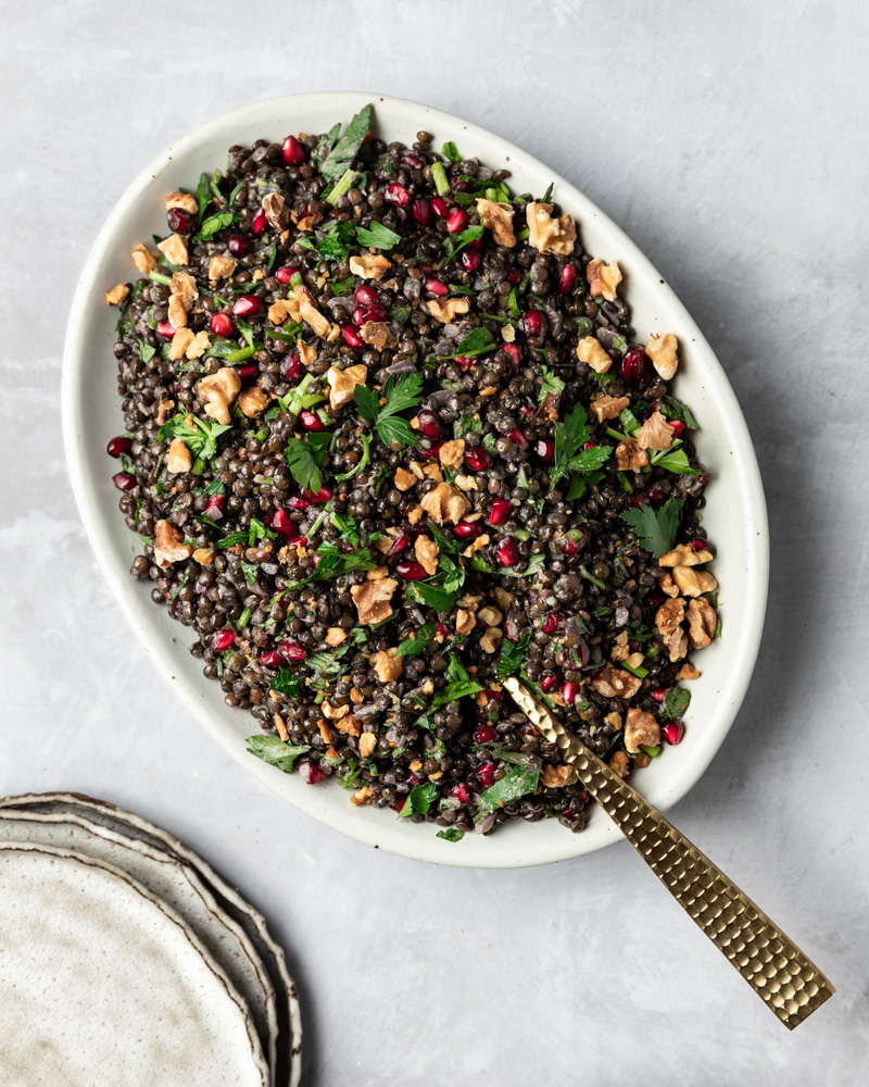 black lentil pomegranate salad on a serving platter