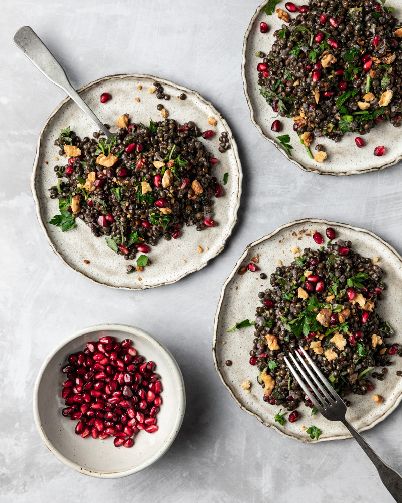 black lentil pomegranate salad on plates