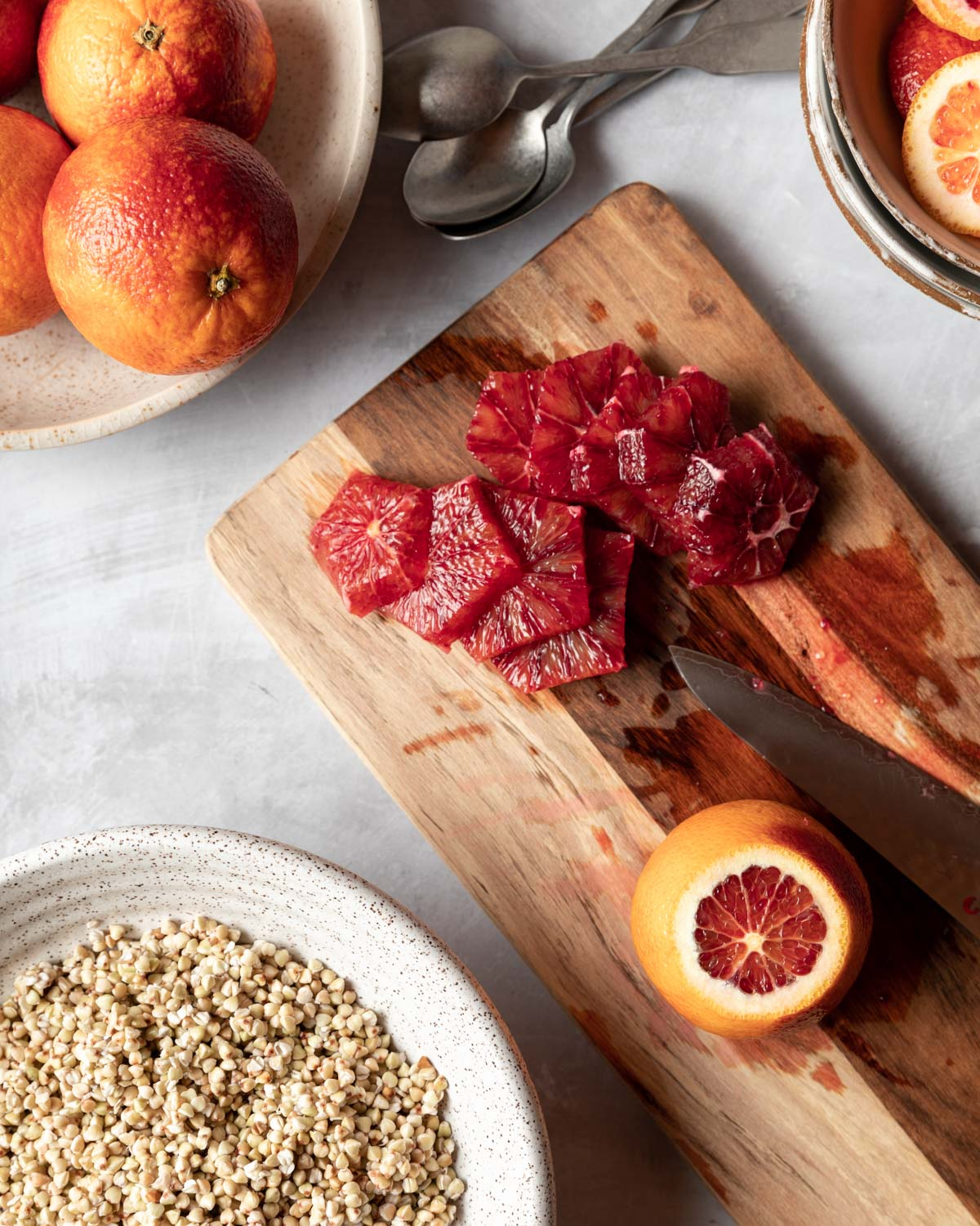 Vibrant blood oranges are peeled and sliced before being placed on top of buckwheat breakfast bowls.