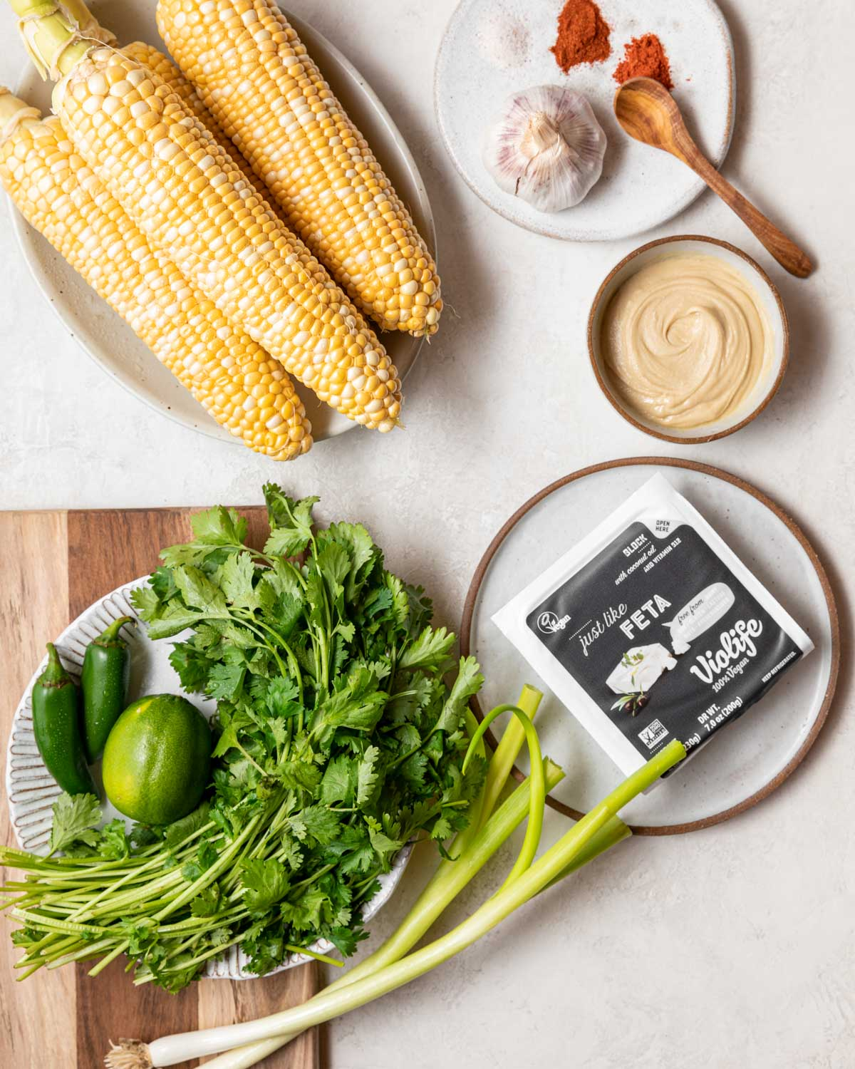 All of the ingredients for the corn salad, including corn on the cob, cashew butter, cilantro, and jalapeño peppers, sit on the counter.