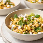 A bowl filled with the finished corn salad and topped with cilantro and vegan feta cheese.