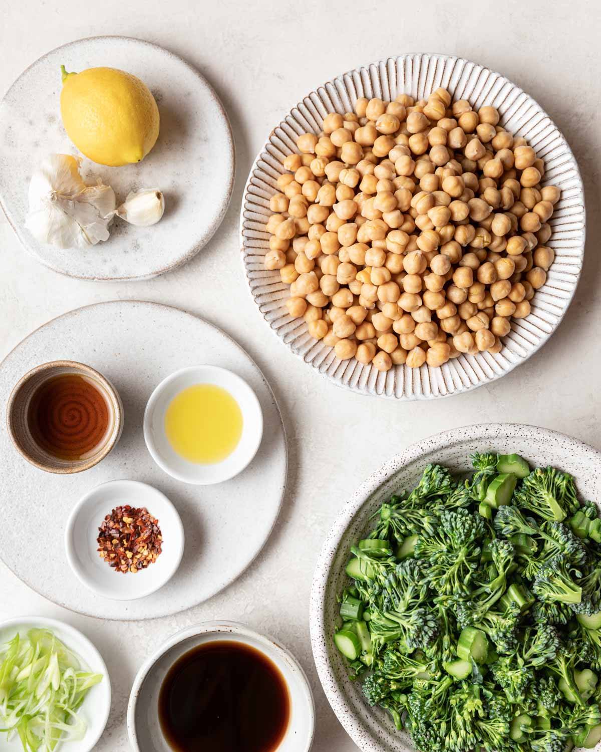 An overhead view of all the ingredients needed for this recipe, including garbanzo beans, chopped broccolini, and seasonings.