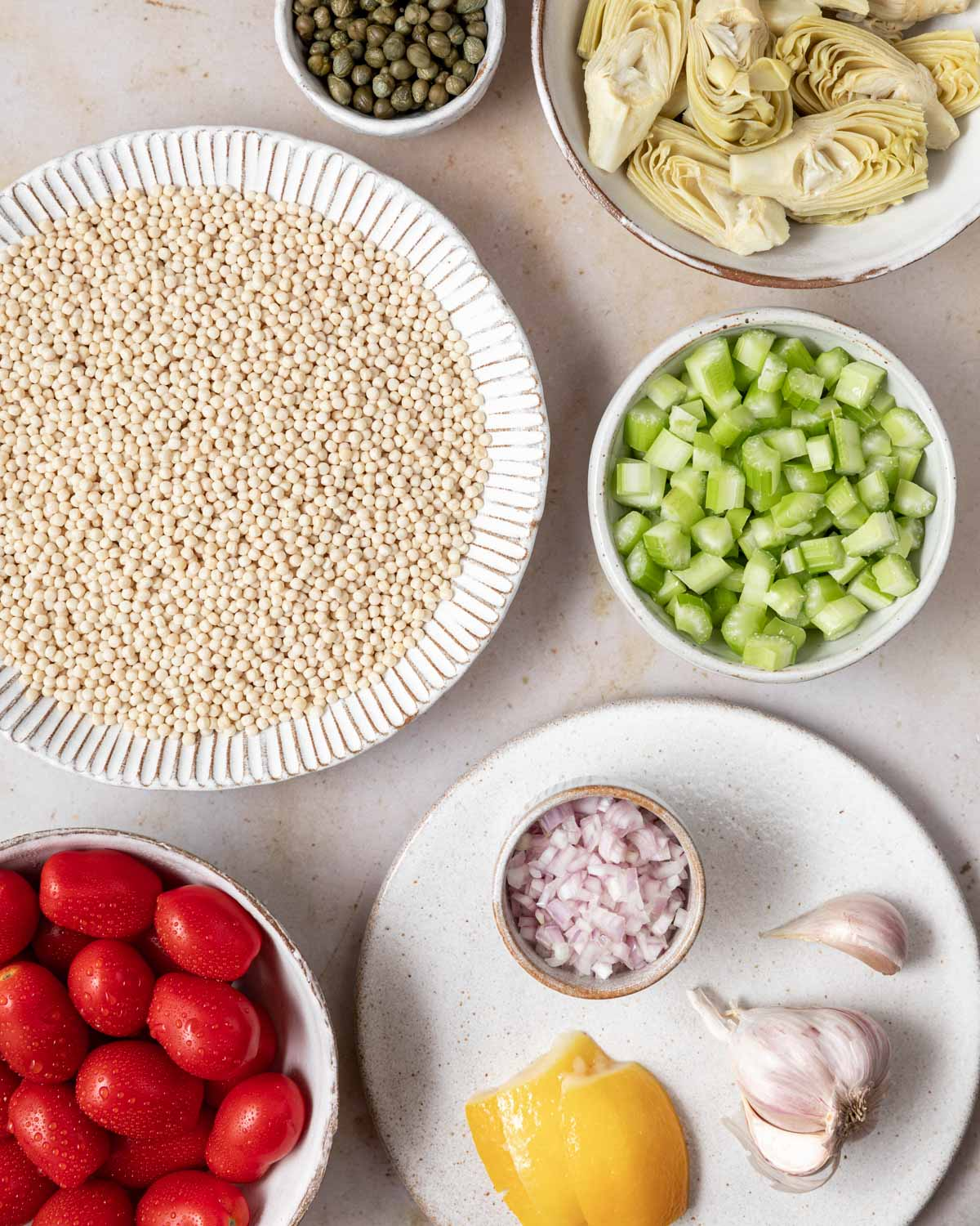 An overhead view of the ingredients needed for this recipe, including pearl couscous, tomatoes, celery, and artichoke hearts