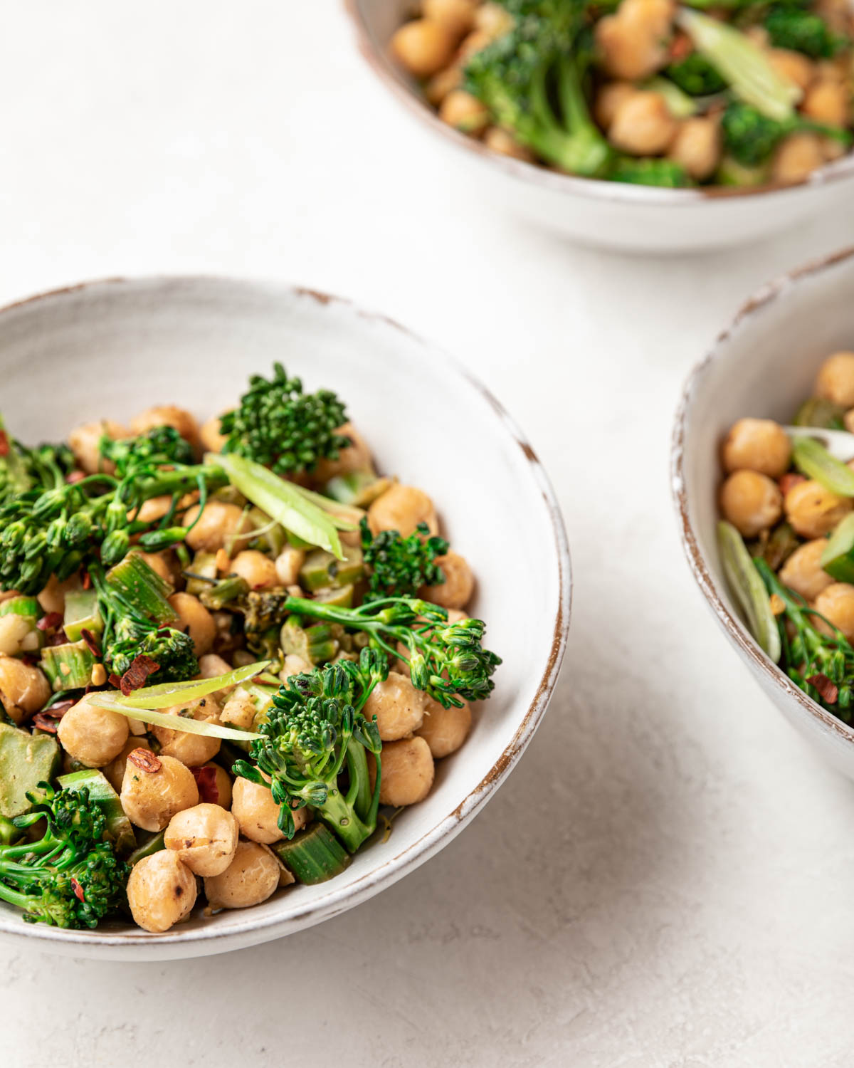 A closeup view of the prepared meal showing bright green broccolini and crispy garbanzo beans